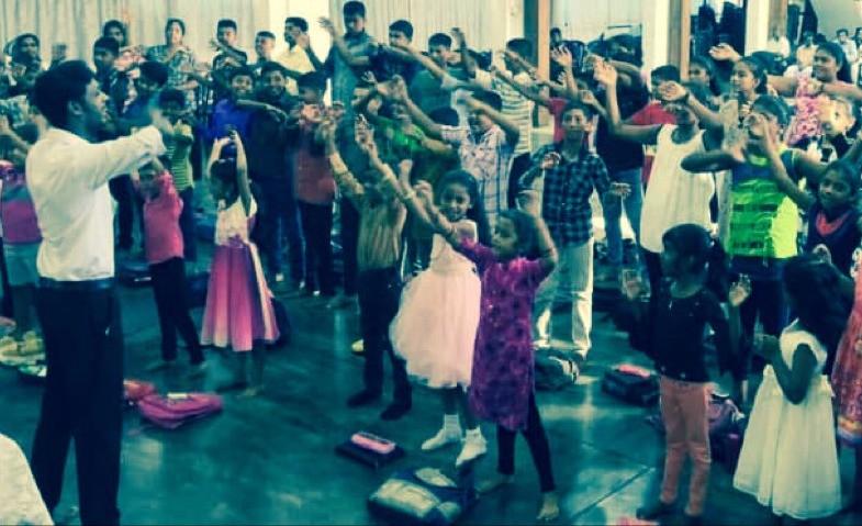 Foto: de kinderen van de zondaggschool staken allemaal hun hand op